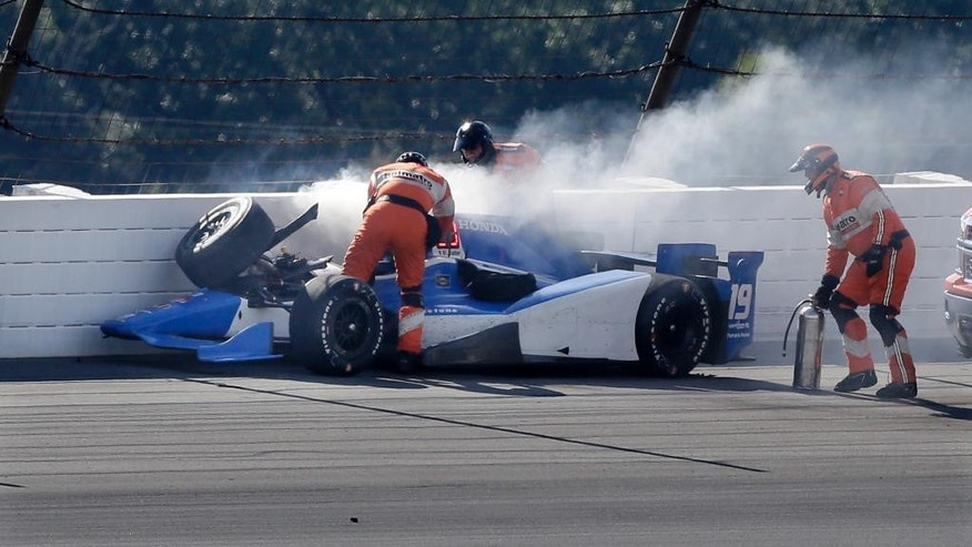 Rescue personnel assist Tristan Vautier, of France, after he collided with Graham Rahal and hit the wall in Turn 3 after colliding during the Pocono IndyCar 500 auto race Sunday, Aug. 23, 2015, in Long Pond, Pa. (AP Photo/Mel Evans)
