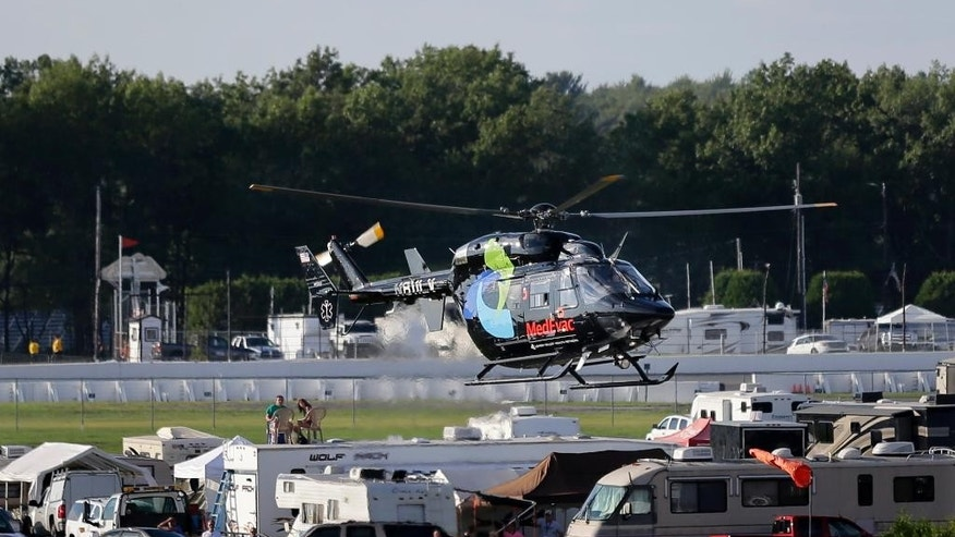 A helicopter lifts off at Pocono Raceway carrying race car driver Justin Wilson, of England, after he was involved in a crash during the Pocono IndyCar 500 auto race Sunday, Aug. 23, 2015, in Long Pond, Pa. (AP Photo/Mel Evans)