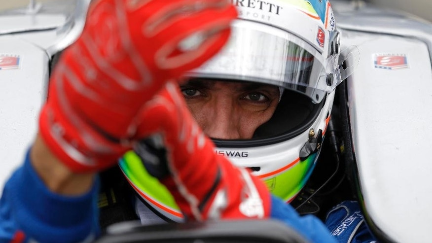 FILE - This is a May 14, 2015, file photo showing Justin Wilson, of England, putting on his gloves as he prepares to drive during practice for the Indianapolis 500 auto race at Indianapolis Motor Speedway in Indianapolis. The British driver was in a coma in critical condition after sustaining a head injury when he was hit by a large piece of debris that broke off another car in the crash-filled race at Pocono Raceway on Sunday, Aug. 23, 2015. (AP Photo/Michael Conroy, File)