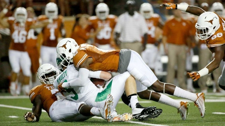 Aug 30, 2014; Austin, TX, USA; Texas Longhorns safety Mykkele Thompson (top) sacks North Texas Mean Green quarterback Andrew McNulty (5) during the first half at Darrell K Royal-Texas Memorial Stadium. Mandatory Credit: Soobum Im-USA TODAY Sports