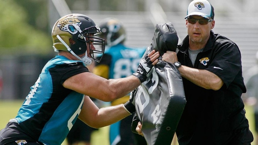 May 28, 2015; Jacksonville, FL, USA; Jacksonville Jaguars center Stefen Wisniewski (61) hits the blocking pad held by strength and conditioning coordinator Tom Myslinski during OTAs at the Florida Blue Health and Wellness Practice Fields. Mandatory Credit: Phil Sears-USA TODAY Sports