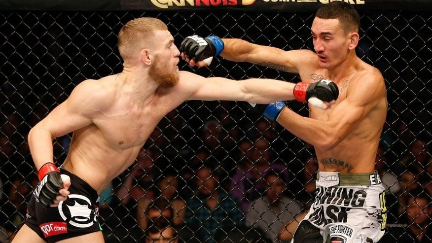 BOSTON, MA - AUGUST 17: (L-R) Conor McGregor punches Max Holloway in their UFC featherweight bout at TD Garden on August 17, 2013 in Boston, Massachusetts. (Photo by Josh Hedges/Zuffa LLC/Zuffa LLC via Getty Images)