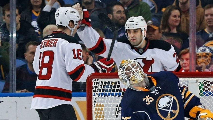Mar 20, 2015; Buffalo, NY, USA; New Jersey Devils right wing Steve Bernier (18) celebrates with center Scott Gomez (21) after Bernier scored on Buffalo Sabres goalie Anders Lindback (35) during the second period at First Niagara Center. Mandatory Credit: Kevin Hoffman-USA TODAY Sports