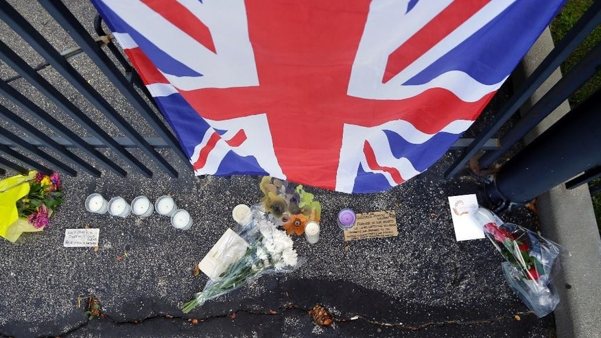 The Union Jack hangs  on the main gate of the Indianapolis Motor Speedway in a memorial to race driver Justin Wilson, of England, Tuesday, Aug. 25, 2015, in Indianapolis.  Wilson died from a head injury suffered when a piece of debris struck him at Pocono Raceway. He was 37. (AP Photo/Michael Conroy)