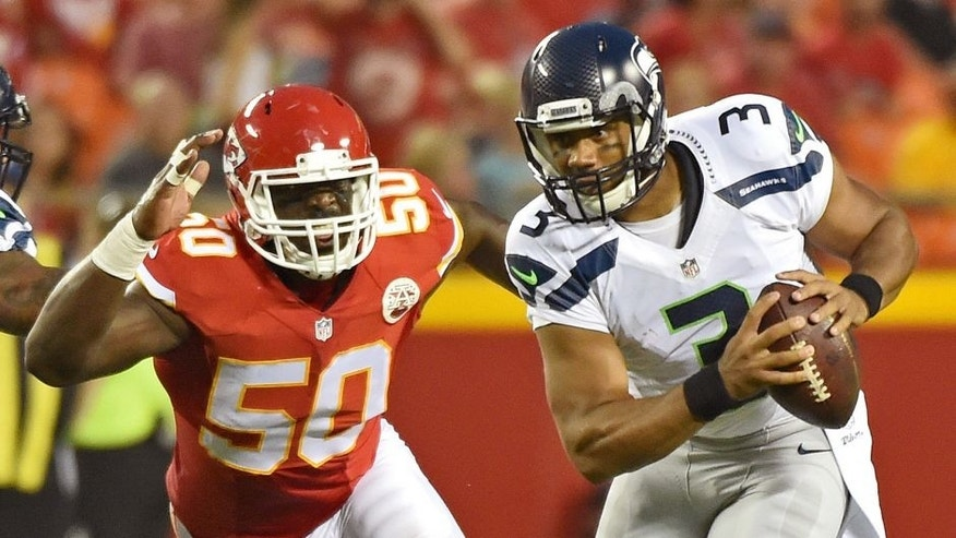 KANSAS CITY, MO - AUGUST 21: Quarterback Russell Wilson #3 of the Seattle Seahawks scrambles away from linebacker Justin Houston #50 of the Kansas City Chiefs during the first half of a preseason game at Arrowhead Stadium on August 21, 2015 in Kansas City, Missouri. (Photo by Peter G. Aiken/Getty Images)