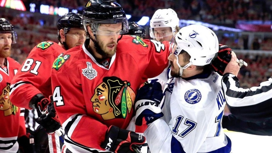 CHICAGO, IL - JUNE 10: Alex Killorn #17 of the Tampa Bay Lightning and Niklas Hjalmarsson #4 of the Chicago Blackhawks get involved after the whistle in the first period during Game Four of the 2015 NHL Stanley Cup Final at the United Center on June 10, 2015 in Chicago, Illinois. (Photo by Tasos Katopodis/Getty Images)
