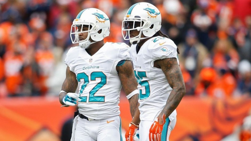 Nov 23, 2014; Denver, CO, USA; Miami Dolphins cornerback Jamar Taylor (22) and Miami Dolphins free safety Louis Delmas (25) during the game against the Denver Broncos at Sports Authority Field at Mile High. Mandatory Credit: Chris Humphreys-USA TODAY Sports