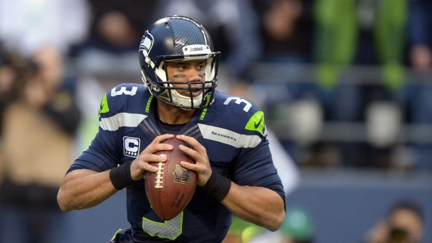 Jan 19, 2014; Seattle, WA, USA; Seattle Seahawks quarterback Russell Wilson (3) drops back to pass against the San Francisco 49ers during the first half of the 2013 NFC Championship football game at CenturyLink Field. Mandatory Credit: Kirby Lee-USA TODAY Sports