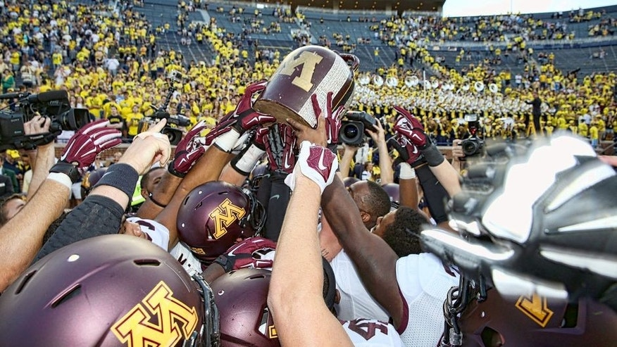 ANN ARBOR, MI - SEPTEMBER 27: Members of the Minnesota Golden Gophers football team celebrate a win over the Michigan Wolverines with the Little Brown Jug and the fans a Michigan Stadium on September 27, 2014 in Ann Arbor, Michigan. The Golden Gophers defeated the Wolvereines 30-14. (Photo by Leon Halip/Getty Images)