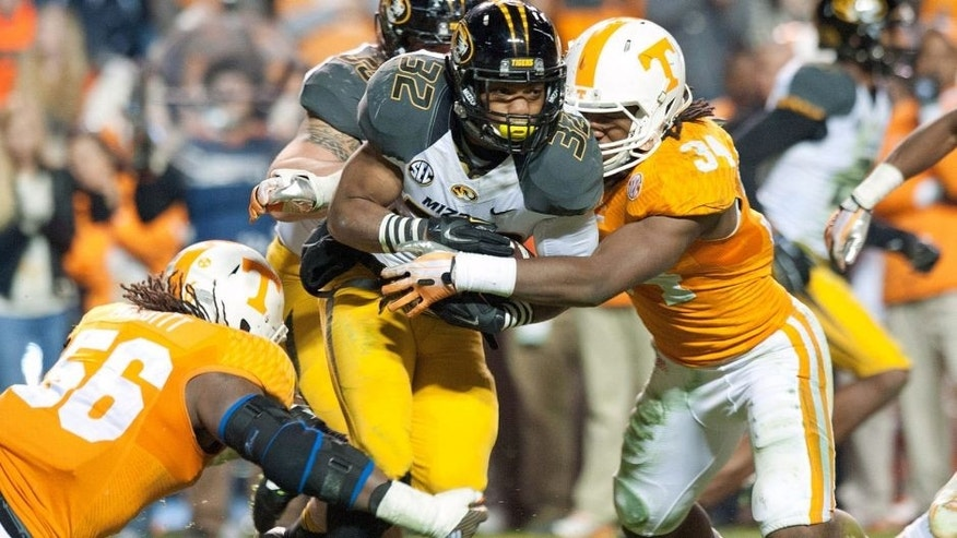 Nov 22, 2014; Knoxville, TN, USA; Missouri Tigers running back Russell Hansbrough (32) rushes against Tennessee Volunteers defensive lineman Curt Maggitt (56) and linebacker Jalen Reeves-Maybin (34) during the first half at Neyland Stadium. Mandatory Credit: Jim Brown-USA TODAY Sports
