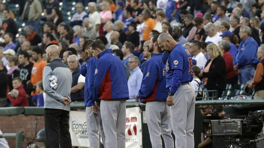 Chicago Cubs players and coaches observe a moment of silence for IndyCar driver Justin Wilson before a baseball game between the San Francisco Giants and the Cubs in San Francisco, Wednesday, Aug. 26, 2015. (AP Photo/Jeff Chiu)