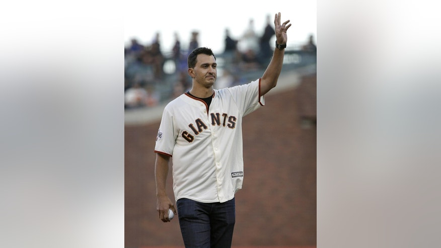 IndyCar driver Graham Rahal waves before throwing out the ceremonial first pitch before a baseball game between the San Francisco Giants and the Chicago Cubs in San Francisco, Wednesday, Aug. 26, 2015. (AP Photo/Jeff Chiu)