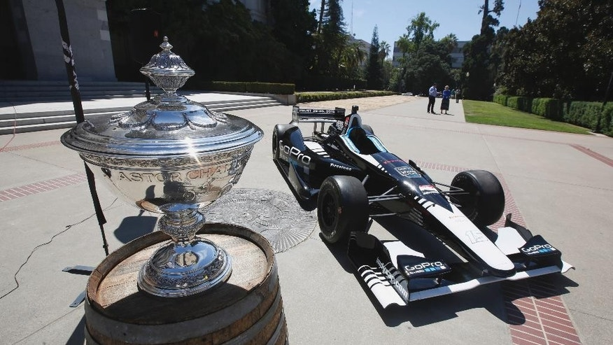 The Astor Cup, awarded to the winner of the IndyCar series, is displayed with a two-seat race car at a news conference about this weekend's  Grand Prix of Sonoma auto race, Wednesday, Aug. 26, 2015, at the Capitol in Sacramento, Calif. (AP Photo/Rich Pedroncelli)