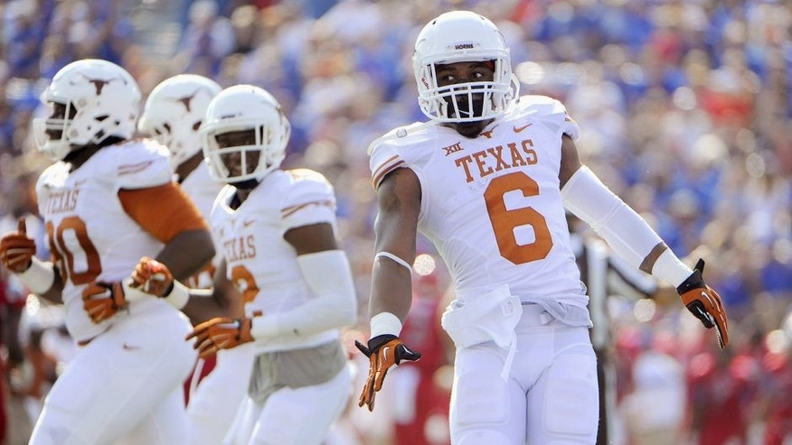 Sep 27, 2014; Lawrence, KS, USA; Texas Longhorns cornerback Quandre Diggs (6) celebrates after intercepting a pass in the end zone against the Kansas Jayhawks in the first half at Memorial Stadium. Mandatory Credit: John Rieger-USA TODAY Sports