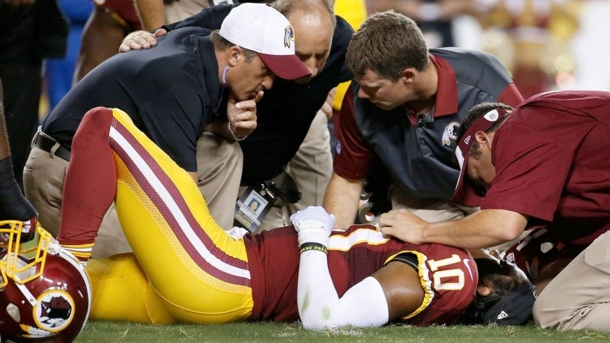Washington Redskins quarterback Robert Griffin III (10) is examined after an injury during the first half of an NFL preseason football game against the Detroit Lions, Thursday, Aug. 20, 2015, in Landover, Md. (AP Photo/Alex Brandon)