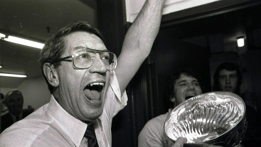 FILE - In this May 17, 1983, file photo, New York Islanders coach Al Arbour celebrates in the locker room as he holds the Stanley Cup after the Islanders won their fourth cup in a row, beating the Edmonton Oilers 4-2 to sweep the series at Nassau Coliseum in Uniondale, N.Y. Arbour, who ranks as the NHL's second-most winningest coach, has died, team officials announced Friday, Aug. 28, 2015. He was 82. The cause of death is unclear, though Arbor was battling a lengthy illness and had been living in Florida. (AP Photo/Pool, File)