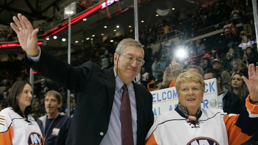 FILE - In this Nov. 3, 2007, file photo, New York Islanders head coach Al Arbour waves to fans as he leaves the ice with his wife Claire after returning to the Islanders to coach his 1500th hockey game, against the Pittsburgh Penguins at the Nassau Coliseum in Uniondale, N.Y. Arbour, who coached the New York Islanders to four consecutive Stanley Cup championships and ranks as the NHL's second-most winningest coach, has died, team officials announced Friday, Aug. 28, 2015. He was 82. The cause of death is unclear, though Arbor was battling a lengthy illness and had been living in Florida.  (AP Photo/Ed Betz, File)