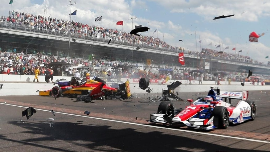 FILE - In this May 10, 2014, file photo, Sebastian Saavedra, left, of Colombia,  is hit by Mikhail Aleshin, of Russia, as Takuma Sato, right, of Japan, drives past on the start of the inaugural Grand Prix of Indianapolis IndyCar auto race at the Indianapolis Motor Speedway in Indianapolis. The IndyCar Series has bounced from one problem to another all season as it scrambles for viewers and new fans. It heads into the season finale this weekend after suffering the worst possible blow: The death of a driver, with Justin Wilson dead at 37 from injuries suffered in a crash.  (AP Photo/Robert Baker, File)