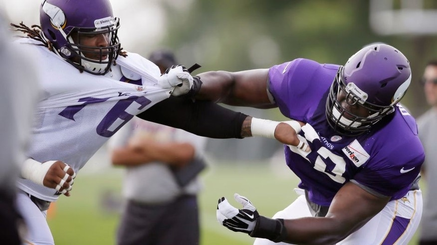 <p>Minnesota Vikings guard Vladimir Ducasse, right, blocks defensive tackle Isame Faciane during an NFL football training camp practice, Wednesday, July 30, 2014, in Mankato, Minn. (AP Photo/Charlie Neibergall)</p>