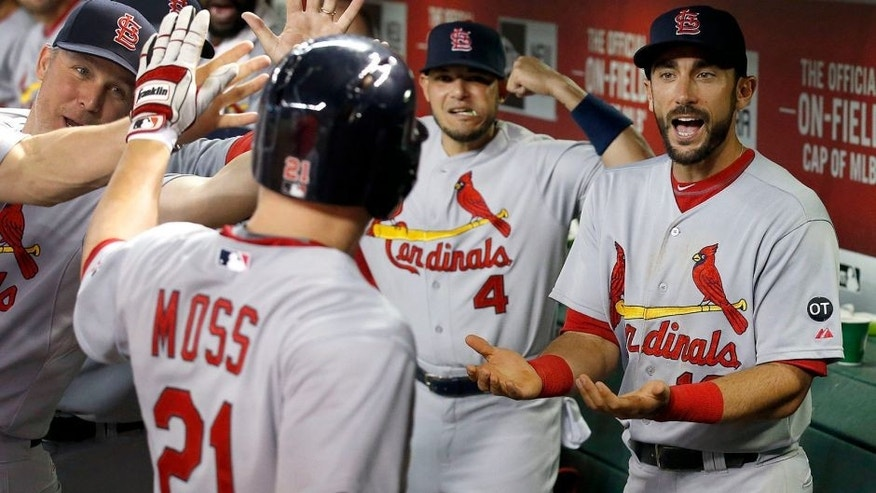 St. Louis Cardinals' Brandon Moss (21) celebrates his two-run home run against the Arizona Diamondbacks with teammates Matt Carpenter, right, and Yadier Molina (4) during the fifth inning of a baseball game Wednesday, Aug. 27, 2015, in Phoenix. (AP Photo/Ross D. Franklin)
