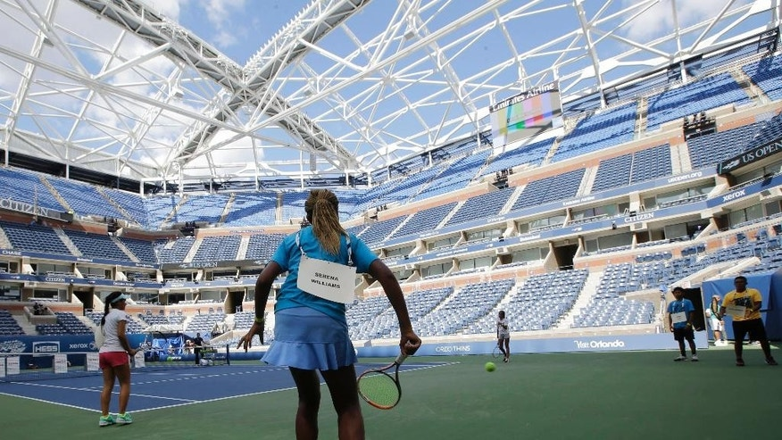 Standing in for Roger Federer and Serena Williams, Nicole Massa, left, and Khadia Ba, center, warm up on Arthur Ashe court during a rehearsal for Arthur Ashe Kids' Day at the USTA Billie Jean King National Tennis Center in New York, Thursday, Aug. 27, 2015.  The framework for a partially-complete retractable roof, above, provides shade for fans, but rain delays could still plague the U.S. Open, a two-week long tennis tournament.  (AP Photo/Kathy Willens)