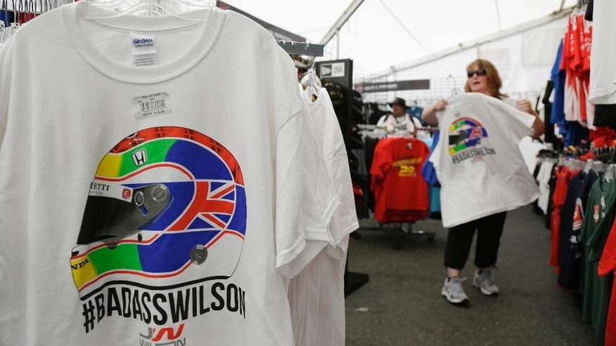 Rita Panike, of Redding, Calif., looks over t-shirts paying tribute to Justin Wilson before practice for the IndyCar auto race Friday, Aug. 28, 2015, in Sonoma, Calif. IndyCar is headed into a somber championship weekend as the paddock mourns the death of popular driver Justin Wilson instead of celebrating its season finale. Wilson, of Great Britain, died Aug. 24 from injuries sustained at Pocono Raceway. (AP Photo/Eric Risberg)