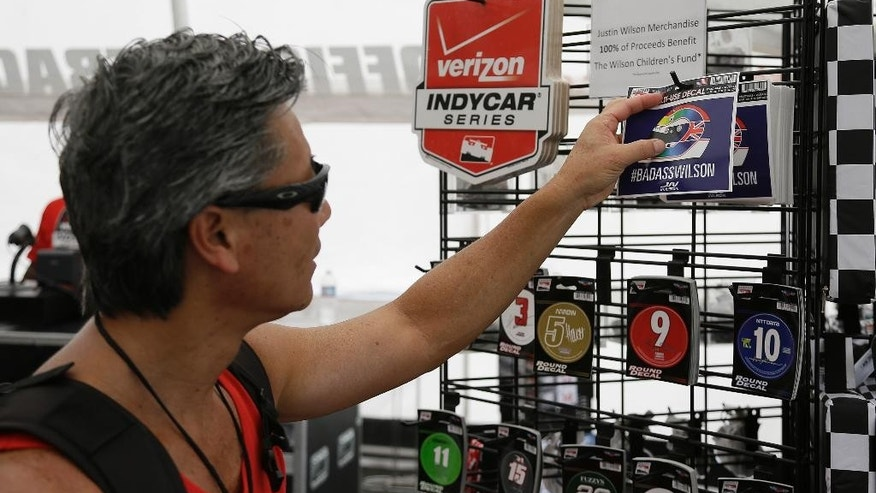 Carl Osaki of Long Beach, Calif., looks over stickers paying tribute to Justin Wilson before practice for the IndyCar auto race Friday, Aug. 28, 2015, in Sonoma, Calif. IndyCar is headed into a somber championship weekend as the paddock mourns the death of popular driver Justin Wilson instead of celebrating its season finale. Wilson, of Great Britain, died Aug. 24 from injuries sustained at Pocono Raceway. (AP Photo/Eric Risberg)