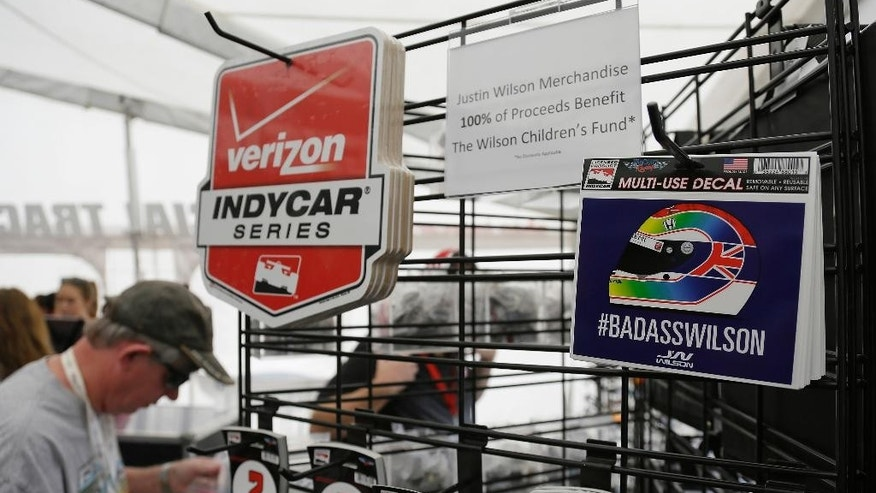 Stickers paying tribute to Justin Wilson are shown for sale in a merchandise tent before practice for the IndyCar auto race Friday, Aug. 28, 2015, in Sonoma, Calif. IndyCar is headed into a somber championship weekend as the paddock mourns the death of popular driver Justin Wilson instead of celebrating its season finale. Wilson, of Great Britain, died Aug. 24 from injuries sustained at Pocono Raceway. (AP Photo/Eric Risberg)