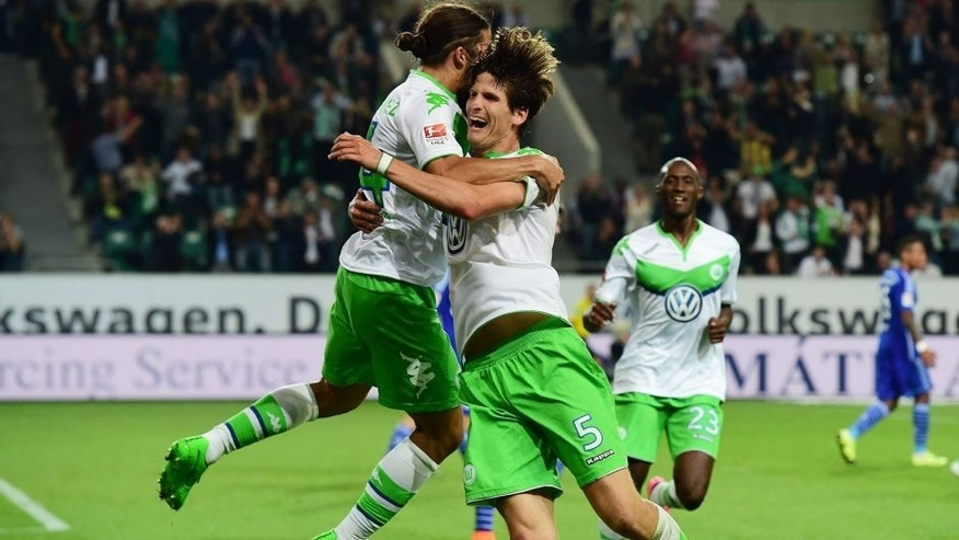 Wolfsburg's Swiss defender Timm Klose (R) celebrates with Wolfsburg's Swiss defender Ricardo Rodriguez after Klose scored the third goal during the German first division Bundesliga football match VfL Wolfsburg vs FC Schalke 04 in Wolfsburg, northern Germany, on August 28, 2015. AFP PHOTO / JOHN MACDOUGALL RESTRICTIONS: DURING MATCH TIME: DFL RULES TO LIMIT THE ONLINE USAGE TO 15 PICTURES PER MATCH AND FORBID IMAGE SEQUENCES TO SIMULATE VIDEO. == RESTRICTED TO EDITORIAL USE == FOR FURTHER QUERIES PLEASE CONTACT DFL DIRECTLY AT + 49 69 650050. (Photo credit should read JOHN MACDOUGALL/AFP/Getty Images)