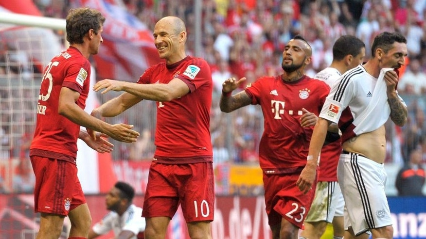 MUNICH, GERMANY - AUGUST 29: Thomas Mueller (L-R), Arjen Robben and Arturo Vidal of FC Bayern Muenchen celebrate scoring the opening goal during the Bundesliga match between FC Bayern Muenchen and Bayer Leverkusen at Allianz Arena on August 29, 2015 in Munich, Germany. (Photo by L. Preiss/Getty Images for FC Bayern)