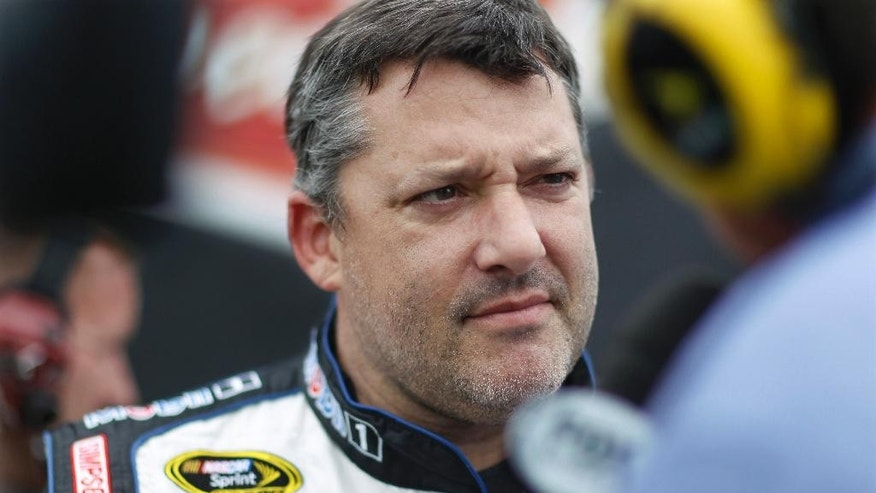 "FILE - In this June 5, 2015, file photo, Tony Stewart listens to a question in the garage area while waiting for his back-up car after hitting the wall at Pocono Raceway during practice for the NASCAR Sprint Cup Series auto race in Long Pond, Pa. The lawyer for a racecar driver who was killed when he was run over by Tony Stewart's car says legal claims by the NASCAR star in response to a lawsuit are ""appalling. Attorney Mark Lanier said in an email Saturday, Aug. 29, 2015, that five other cars drove around Kevin Ward, Jr., as he walked on the dirt race track during a yellow caution flag in August 2014, before Stewart ""revved his engine and ran him over."" (AP Photo/Mel Evans, File)"