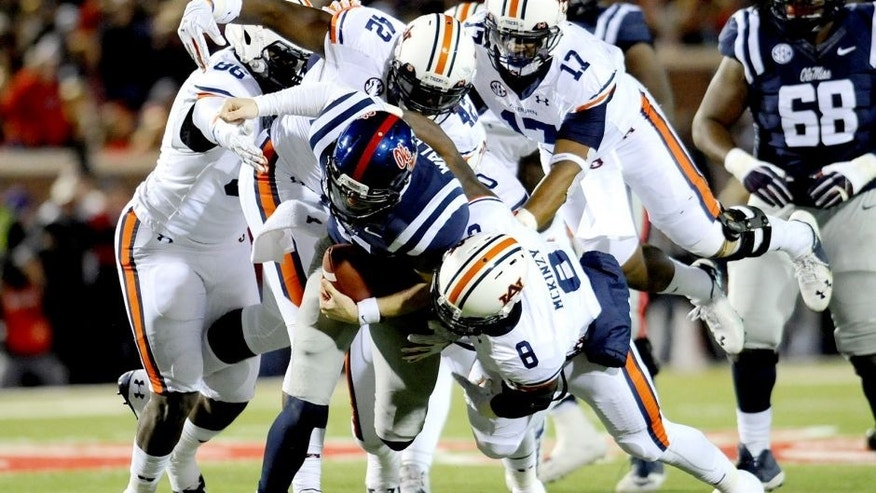Nov 1, 2014; Oxford, MS, USA; Ole Miss Rebels quarterback Bo Wallace (14) is tackled by Auburn Tigers linebacker Cassanova McKinzy (8) during the second quarter at Vaught-Hemingway Stadium. Mandatory Credit: Shanna Lockwood-USA TODAY Sports