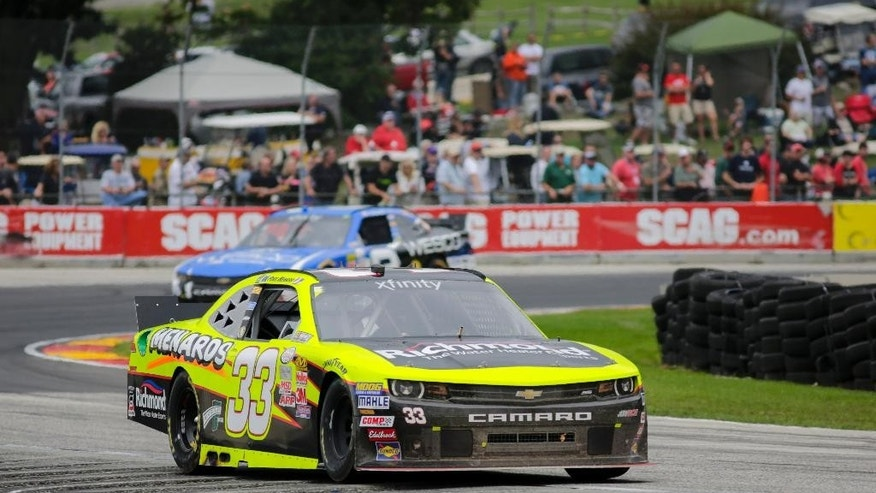 Paul Menard competes in the NASCAR Xfinity Series auto race Saturday, Aug. 29, 2015, at Road America in Elkhart Lake, Wis. Menard won the race, Ryan Blaney placed second and Brian Scott took third. (AP Photo/Andy Manis)