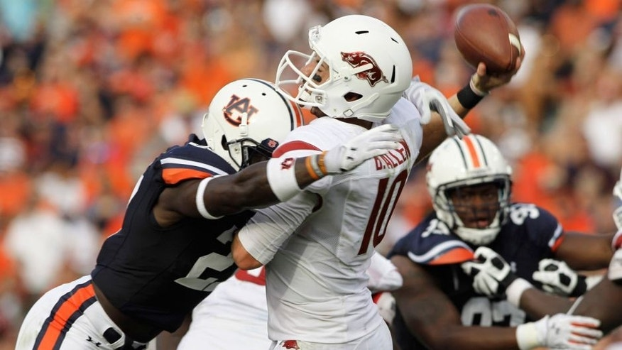 Aug 30, 2014; Auburn, AL, USA; Arkansas Razorbacks quarterback Brandon Allen (10) is hit by Auburn Tigers defensive back Robenson Therezie (27) during the second half at Jordan Hare Stadium. Mandatory Credit: John Reed-USA TODAY Sports