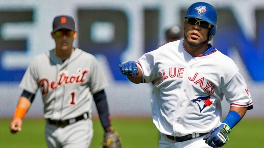 Toronto Blue Jays' Edwin Encarnacion, right, rounds the bases after hitting a solo home run off Detroit Tigers starting pitcher Alfredo Simon as Tigers' shortstop Jose Iglesias, left, looks on during first-inning baseball game action in Toronto, Sunday, Aug. 30, 2015. (Chris Young/The Canadian Press via AP) MANDATORY CREDIT