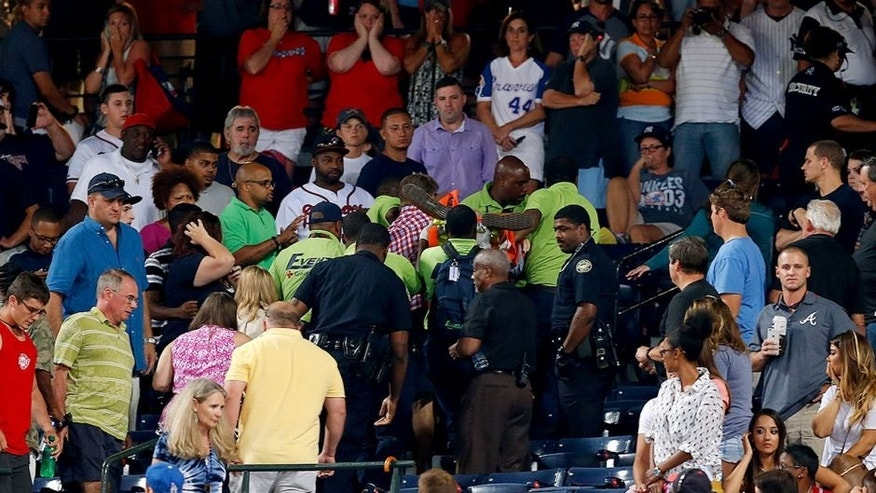 ATLANTA, GA - AUGUST 29: Emergency medical staff help a fan that fell from the upper deck of Turner Field during the game between the Atlanta Braves and the New York Yankees on August 29, 2015 in Atlanta, Georgia. (Photo by Mike Zarrilli/Getty Images)