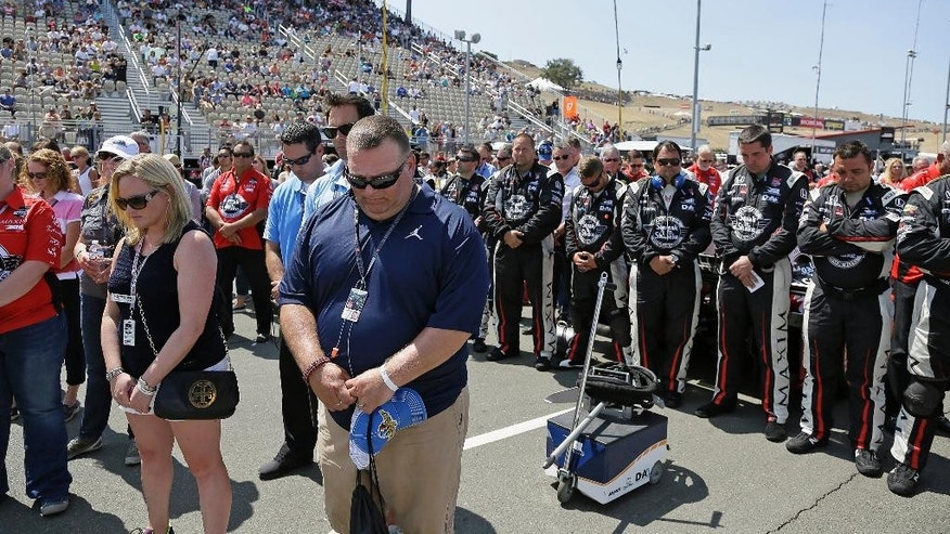 Spectators and the pit crew of Graham Rahal, at right, stand during a moment of silence for Justin Wilson before the IndyCar Grand Prix of Sonoma auto race Sunday, Aug. 30, 2015, in Sonoma, Calif. Wilson, of England, died Aug. 24 from injuries sustained at Pocono Raceway. (AP Photo/Eric Risberg)