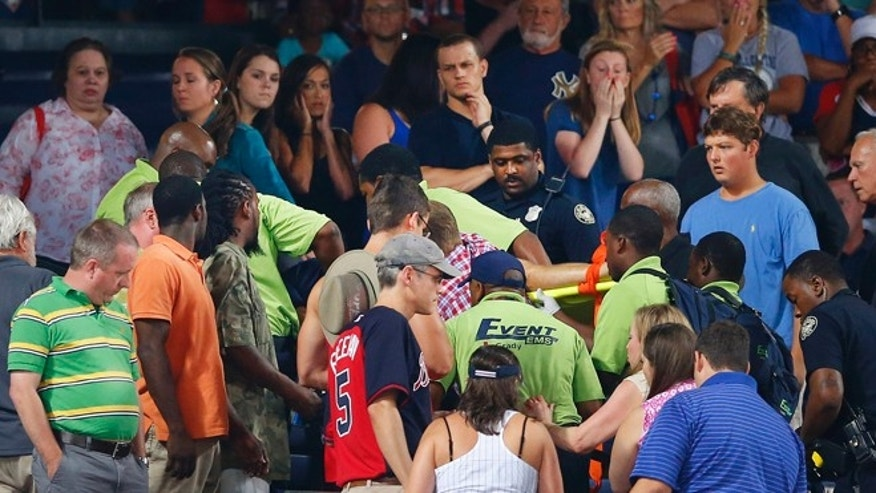 Rescue workers carry an injured fan from the stands at Turner Field during a baseball game between Atlanta Braves and New York Yankees Saturday, Aug. 29, 2015, in Atlanta. A fan has been given emergency medical treatment and been taken to a hospital after falling from the upper deck into the lower-level stands at Turner Field during a game between the New York Yankees and Atlanta Braves. (AP Photo/John Bazemore)