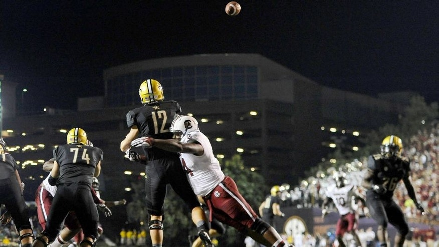 Sep 20, 2014; Nashville, TN, USA; Vanderbilt Commodores quarterback Wade Freebeck (12) is hit as he passes the ball during the first half against the South Carolina Gamecocks at Vanderbilt Stadium. Mandatory Credit: Christopher Hanewinckel-USA TODAY Sports
