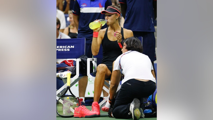 A trainer tends to Vitalia Diatchenko of Russia during her first round match against Serena Williams at the U.S. Open Tennis  tournament in New York, Monday, Aug. 31, 2015. Diatchenko stopped playing due to an injury as she was losing to Williams 6-0, 2-0. (AP Photo/Kathy Willens)