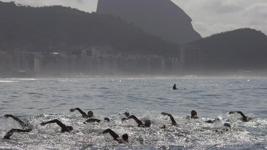 FILE -In this Aug. 22, 2015 file photo, backdropped by Sugar Loaf Mountain, athletes compete in the men's marathon swimming test event, ahead of the Rio 2016 Olympic Games, off Copacabana Beach, Rio de Janeiro, Brazil. Rio's sewage-filled waters are more than just a health risk. For open-water swimmers at the Olympics next year on famous Copacabana Beach, avoiding the bacteria and viruses will become part of the race strategy and could determine who gets a medal, and who doesn't. (AP Photo/Leo Correa, File)