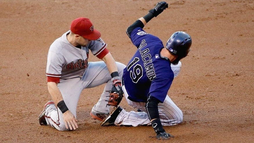DENVER, CO - AUGUST 31: Charlie Blackmon #19 of the Colorado Rockies slides into second with a stolen base after a video replay determined shortstop Chris Owings #16 of the Arizona Diamondbacks missed the tag and reversed the call in the first inning at Coors Field on August 31, 2015 in Denver, Colorado. (Photo by Doug Pensinger/Getty Images)