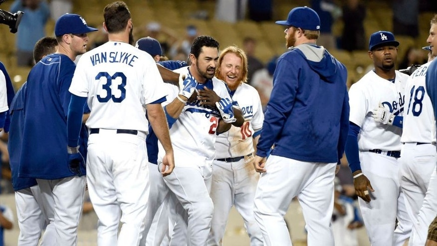 Aug 31, 2015; Los Angeles, CA, USA; Los Angeles Dodgers first baseman Adrian Gonzalez (23) celebrates with teammates after hitting a walk off during the fourteenth inning against the San Francisco Giants at Dodger Stadium. Mandatory Credit: Richard Mackson-USA TODAY Sports