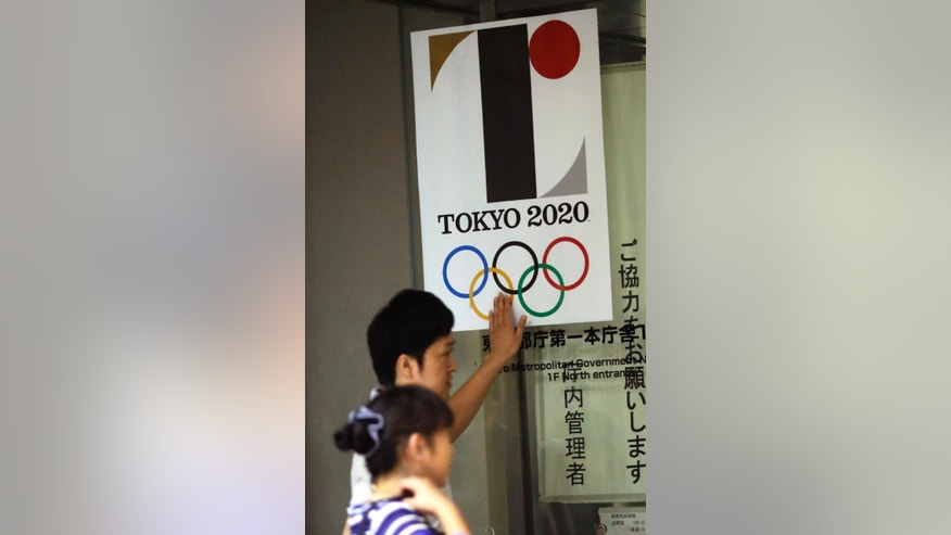 A visitor touches a logo of Tokyo Olympic Games 2020 at the Tokyo Metropolitan Government building in Tokyo Tuesday, Sept. 1, 2015. Tokyo Olympic organizers on Tuesday decided to scrap the logo for the 2020 Games following another allegation its Japanese designer might have used copied materials. (AP Photo/Eugene Hoshiko)