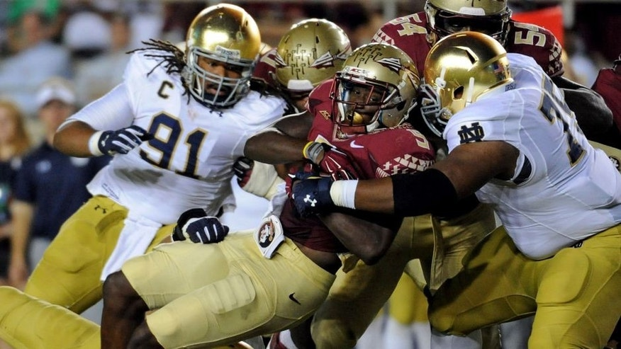Oct 18, 2014; Tallahassee, FL, USA; Florida State Seminoles running back Karlos Williams (9) runs the ball and is tackled by Notre Dame Fighting Irish defensive lineman Daniel Cage (75) during the first half at Doak Campbell Stadium. Mandatory Credit: Melina Vastola-USA TODAY Sports