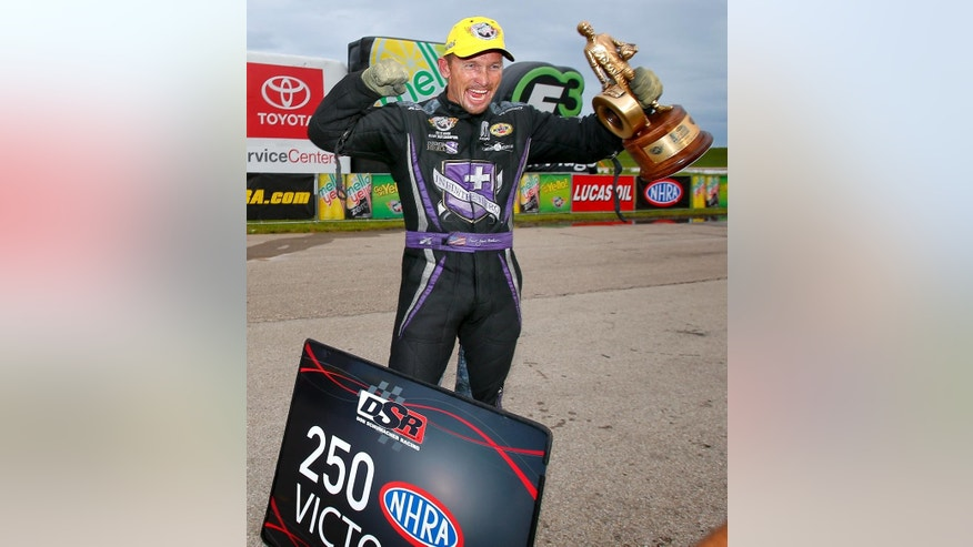 """FILE - In this May 24, 2015, file photo, Funny Car driver """"Fast"""" Jack Beckman celebrates after winning the 2015 NHRA Kansas Nationals at Heartland Park in Topeka, Kan. Beckman is Funny Car's fastest driver. With speeds topping 322 mph, he's been breaking records and breaking down barriers. At this weekend's U.S. Nationals, Beckham is looking to add another title to his resume: A winner at Indianapolis. (Chris Neal/The Topeka Capital-Journal via AP, File)  MANDATORY CREDIT"""