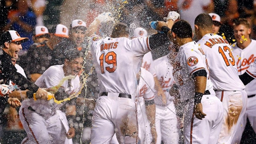 Baltimore Orioles' Chris Davis (19) is greeted as he crosses home plate after hitting a solo home run during the 11th inning of a baseball game against the Tampa Bay Rays, Wednesday, Sept. 2, 2015, in Baltimore. Baltimore won 7-6. (AP Photo/Patrick Semansky)