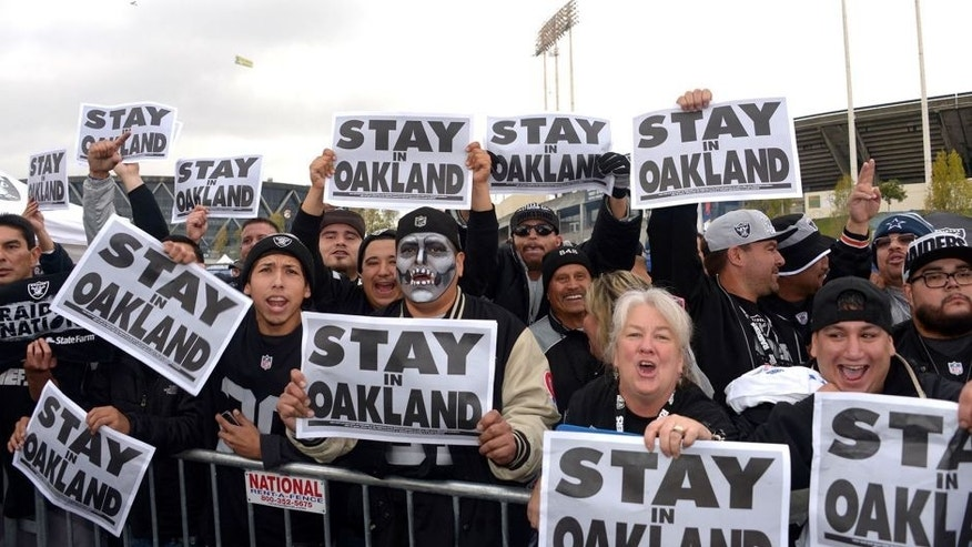 """Nov 20, 2014; Oakland, CA, USA; Oakland Raiders fans tailgate while holding signs the read """"Stay in Oakland"""" before the NFL football game against the Kansas City Chiefs at O.co Coliseum. Mandatory Credit: Kirby Lee-USA TODAY Sports"""