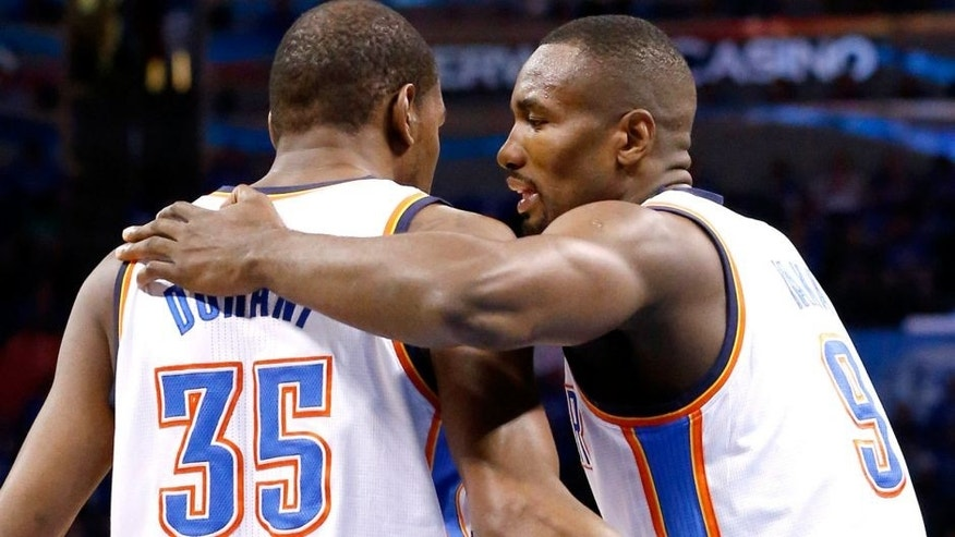 Oklahoma City Thunder forward Serge Ibaka talks with teammate Kevin Durant (35) after Durant was awarded a foul shot in the first quarter of Game 3 of an NBA basketball playoff series of the Western Conference finals against the San Antonio Spurs, Sunday, May 25, 2014, in Oklahoma City. (AP Photo/Sue Ogrocki)