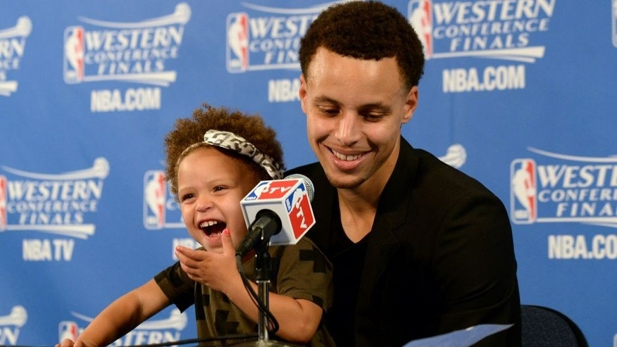 OAKLAND, CA - MAY 19: Stephen Curry #30 of the Golden State Warriors and his daughter Riley talking with the media at a press conference after the game against the Houston Rockets during Game One of the Western Conference Finals during the NBA Playoffs on May 19, 2015 at ORACLE Arena in Oakland, California. NOTE TO USER: User expressly acknowledges and agrees that, by downloading and or using this Photograph, user is consenting to the terms and conditions of the Getty Images License Agreement. Mandatory Copyright Notice: Copyright 2015 NBAE (Photo by Noah Graham/NBAE via Getty Images)